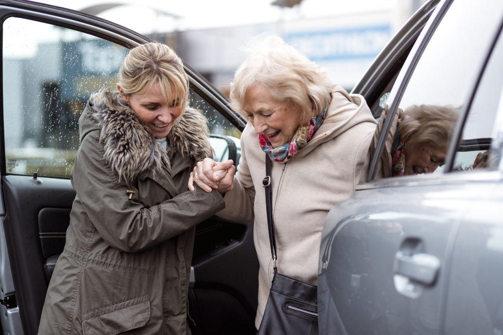 Fotobeschreibung: Eine junge Frau hilft einer Seniorin aus dem Auto.