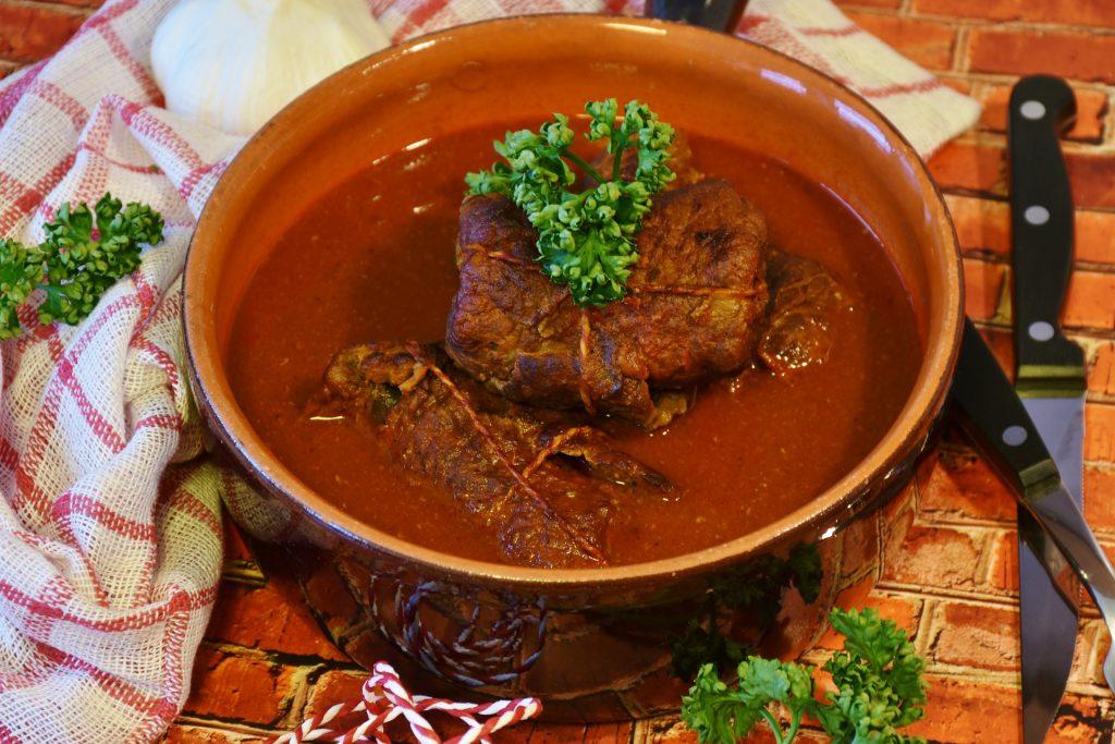 Bildtext: Zu sehen ist eine Nahaufnahme einer Tonschale in der eine Schweineroulade in einer dunklen Soße liegt. Die Roulade ist mit Petasilie garniert.