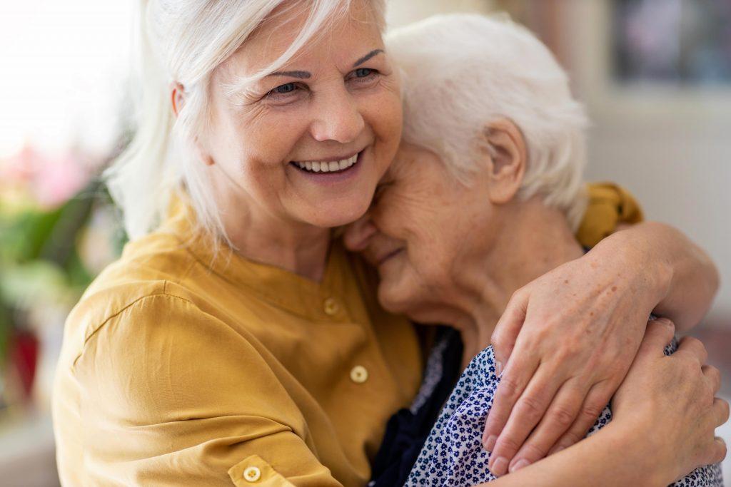 Bildbeschreibung: Nahaufnahme von zwei älteren Frauen, die sich innig in den Armen liegen. Beide lächeln.