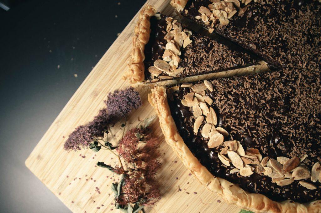 Bildbeschreibung: Nahaufnahme eines Hefekuchens mit dunkler Birnenmusfüllung. Der Kuchen liegt auf einem Holzbrettchen und ist mit geraspelten Nüssen garniert.