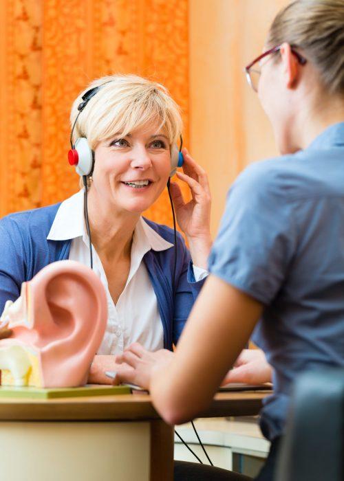 Fotobeschreibung: Eine Frau mittleren Alters sitzt bei einem Hörgeräteakustiker am Schreibtisch und macht einen Hörtest.