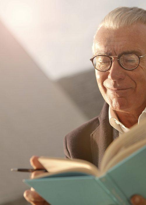 Fotobeschreibung: Nahaufnahme eines freundlich lächelnden Senioren mit Lesebrille, der ein aufgeschlagenes Buch in den Händen hält.